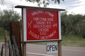 A roadside sign outside a farm in Amado, Ariz., beckons travelers to buy local meat and produce.