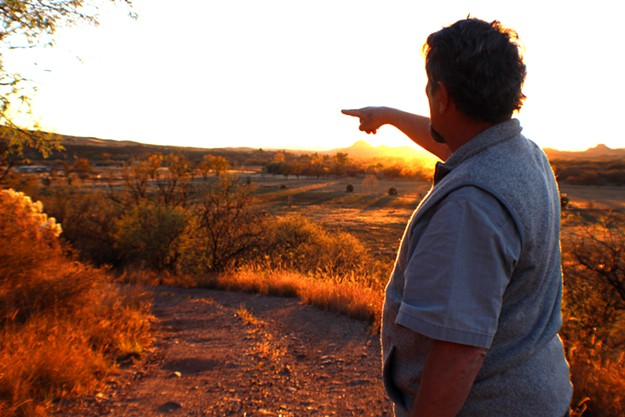 Gary Nabhan points to the Native Seeds/SEARCH Conservation Farm in the distance.