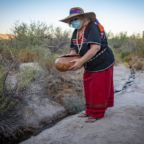 Eleanor Ortega fills a gourd with water from the Quitobaquito Springs before a tribal ceremony at Organ Pipe National Momument. Photo by Josh Galemore.